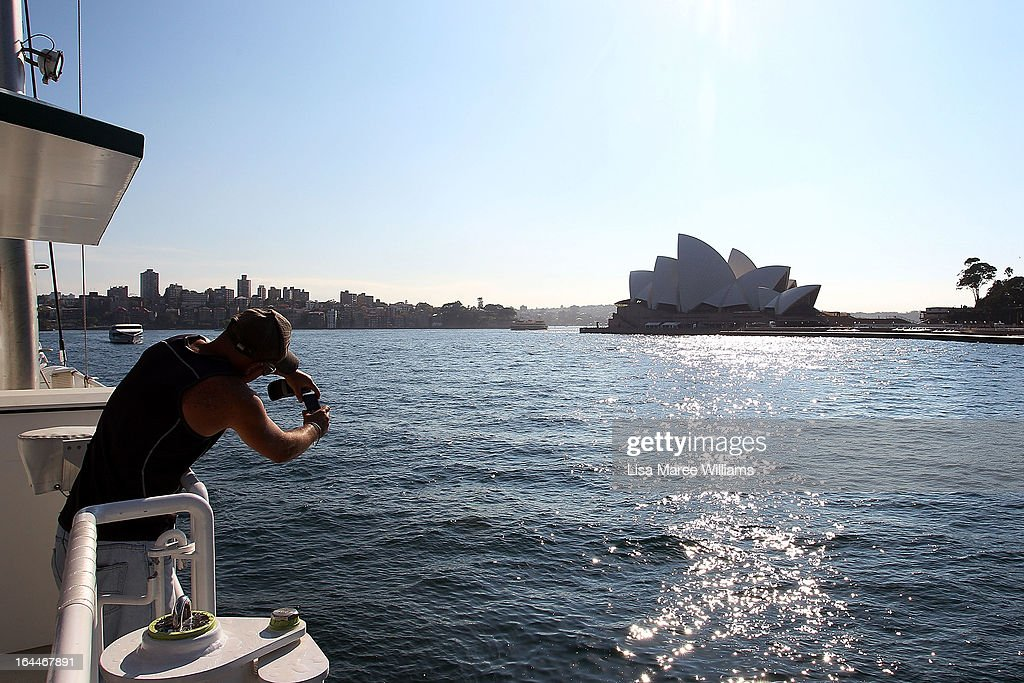 A visitor takes a photograph from the deck of the Greenpeace Rainbow Warrior at the Overseas Passenger Terminal in Circular Quay on March 24, 2013 in Sydney, Australia. The vessel is in Australia to protest new coal mines set to open near the Great Barrier Reef, and is opening for public viewing at ports across the country. The original Rainbow Warrior was bombed and sunk in Auckland Harbour in 1985 by two French intelligent agents, killing a Dutch photographer on board.