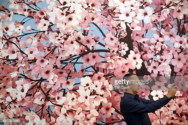 A visitor takes a photograph next to an art work by Thomas Demand entitled 'Hanami' during the VIP and press day at the Frieze Art Fesival on October...