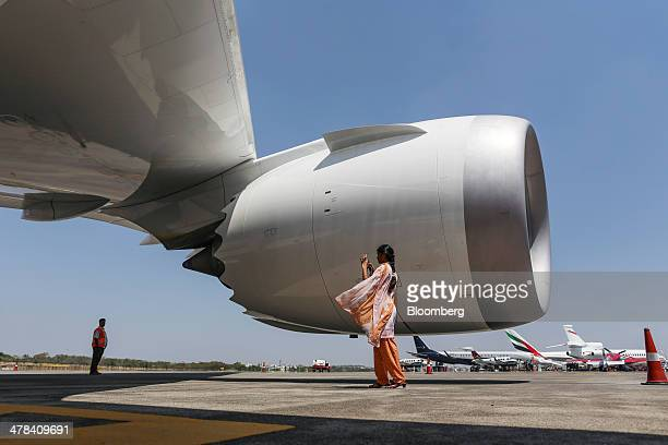 A visitor takes a photograph of a Boeing Co 787 Dreamliner aircraft operated by Air India Ltd as its sits on display during the India Aviation 2014...