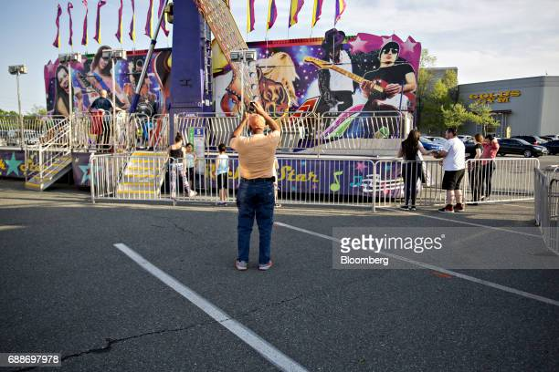 A visitor takes a photograph of a ride in the parking lot of the Marley Station Mall during the Dreamland Amusements carnival in Glen Burnie Maryland...