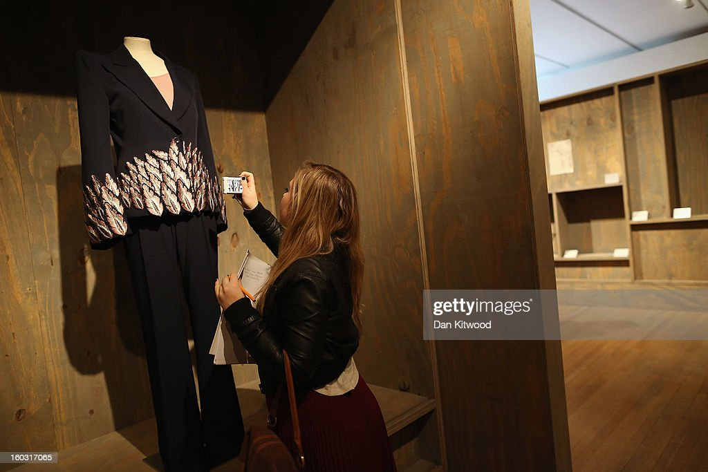 A visitor takes a photograph of an Alexander McQueen Trouser suit during a photocall at The Design Museum on January 29, 2013 in London, England. Design Museum trustee Lady Ritblat has donated over 400 fashion items to the museum including dresses by Alexander McQueen and Chanel, and go on show in the Design Museum's permanent collection from today.