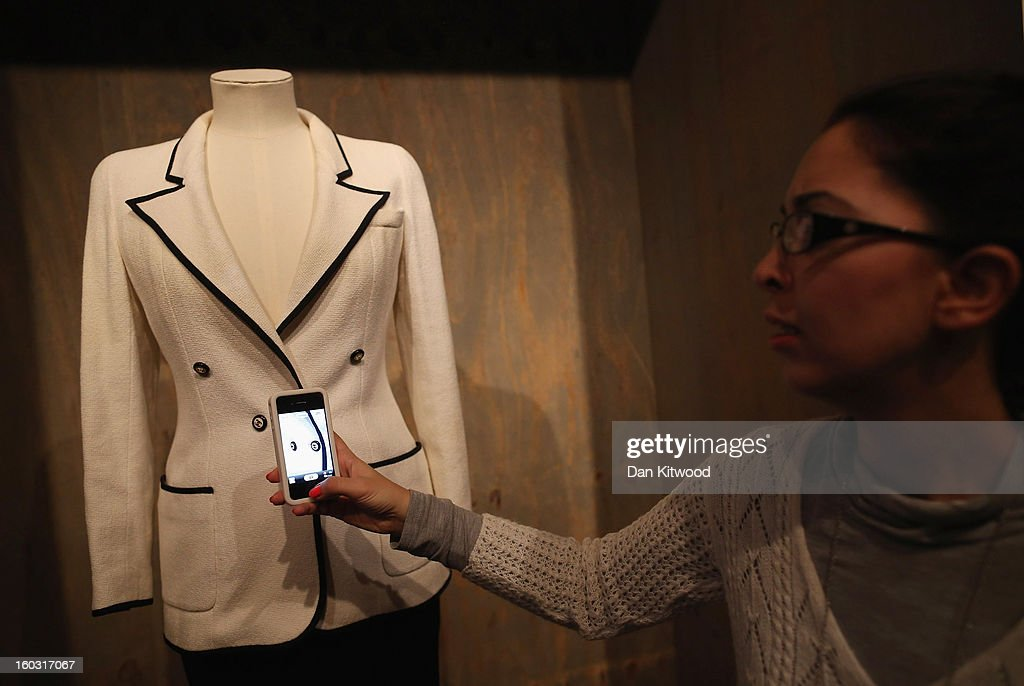 A visitor takes a photograph of buttons on a Chanel dress during a photocall at The Design Museum on January 29, 2013 in London, England. Design Museum trustee Lady Ritblat has donated over 400 fashion items to the museum including dresses by Alexander McQueen and Chanel, and go on show in the Design Museum's permanent collection from today.