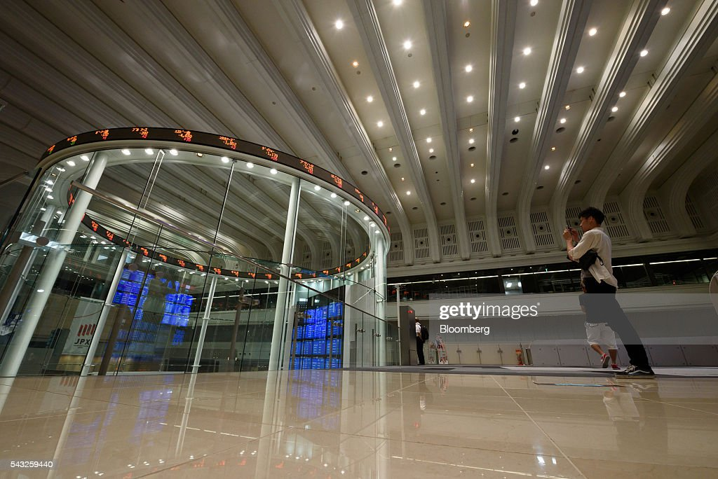 A visitor takes a photograph of stock tickers displayed on the trading floor of the Tokyo Stock Exchange (TSE), operated by Japan Exchange Group Inc. (JPX), in Tokyo, Japan, Monday, June 27, 2016. The yen was closing in on 99 per dollar at one point Friday and headed for its biggest gain since it was freely floated in February 1973, as Britain's vote to leave the European Union prompted investors to flee global markets and seek safety in Japanese government bonds. Photographer: Akio Kon/Bloomberg via Getty Images