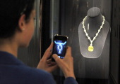 A visitor takes a photograph of the 'Tiffany Diamond' on display at the Tiffany and Co jewellery store on on the Champs Elysees on June 10 on the day...