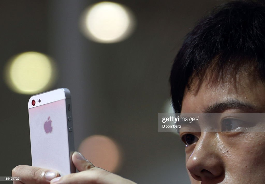 A visitor takes a photograph using an Apple Inc. iPhone at the Wuhan Motor Show 2013 in Wuhan, China, on Saturday, Oct. 19, 2013. The show will be held through Oct. 23. Photographer: Tomohiro Ohsumi/Bloomberg via Getty Images