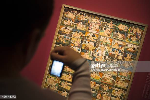 A visitor takes a picture as he visits the exhibition The KamaSutra spirituality and erotism in Indian art at the Paris' pinacotheque on October 1...