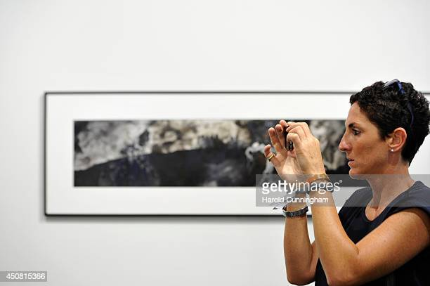 A visitor takes a picture in the gallery section of Art Basel on June 18 2014 in Basel Switzerland Art Basel one of the most prestigious art fair in...