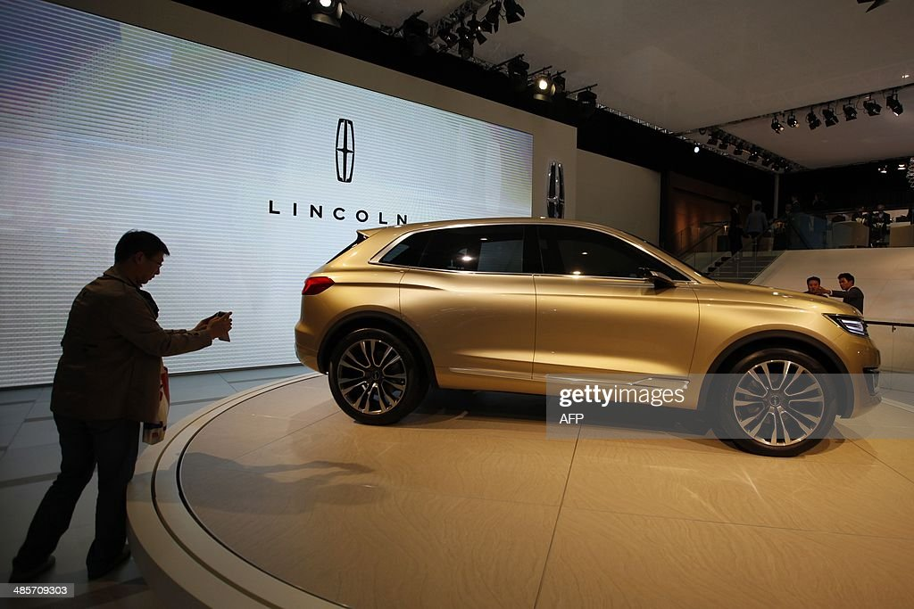A visitor takes a picture of a Lincoln car on display at the China International Exhibition Center new venue during the 'Auto China 2014' Beijing International Automotive Exhibition in Beijing on April 20, 2014. Leading automakers are gathering in Beijing for the kickoff of China's biggest car show, but lackluster growth and environmental restrictions in the world's largest car market have thrown uncertainty into the mix. More than 1,100 vehicles are being showcased at the auto show, which opens to the public on April 21. CHINA OUT AFP PHOTO