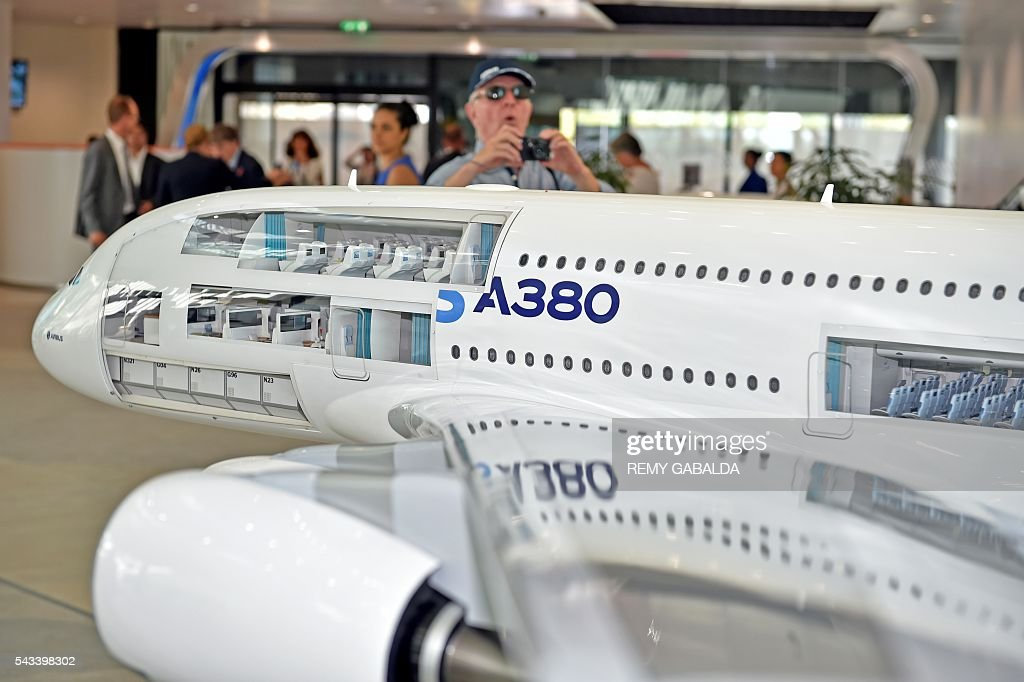 A visitor takes a picture of a model of the Airbus plane A380 during the inauguration ceremony of the new headquarters of Airbus Group on June 28, 2016 in Blagnac, on the outskirts of Toulouse. / AFP / Rémy GABALDA