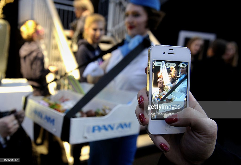 A visitor takes a picture of a PanAm hostess with his smartphone at Mercedes-Benz Fashion Week Autumn/Winter 2013/14 at The Brandenburg Gate on January 16, 2013 in Berlin, Germany.