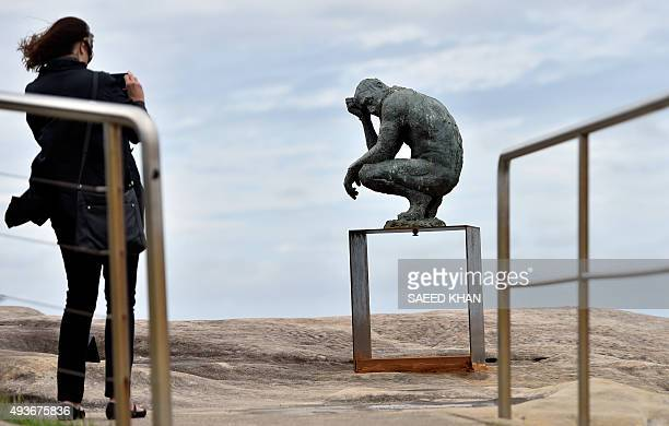A visitor takes a picture of a sculpture by British artist Laurence Edwards at the 'Sculpture by the Sea' exhibition which runs along the Bondi to...