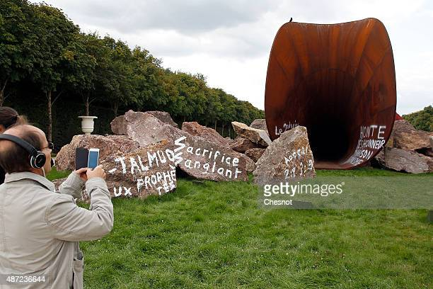 A visitor takes a picture of an artwork named 'Dirty Corner' by British contemporary artist of Indian origin Anish Kapoor vandalized for the second...