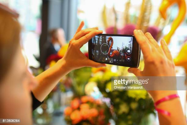 A visitor takes a picture of flowers by using a smartphone during the 'Kians Garden Flower Shop' Opening Event at Kantstrasse on July 11 2017 in...