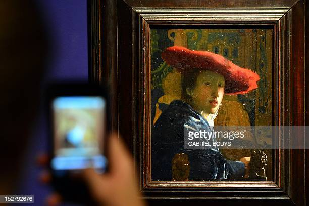 A visitor takes a picture of 'Girl with the Red Hat' by Dutch artist Johannes Vermeer on September 26 2012 during the media preview of the exhibition...