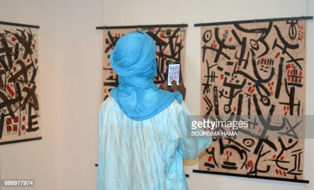 A visitor takes a picture of paintings by Tuareg poet and painter Hawad on April 6 in Niamey The BoubouHama National Museum in Niamey and the...