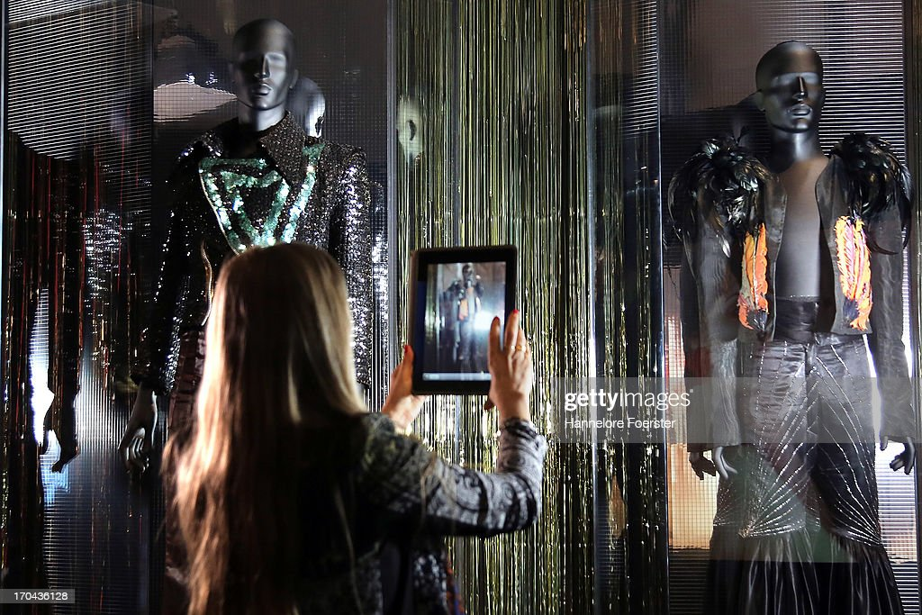 A visitor takes a picture of the Antony Price jackets for Bryan Ferry display during the GLAM-Exhibition at Schirn Kunsthalle on June 13, 2013 in Frankfurt am Main, Germany.