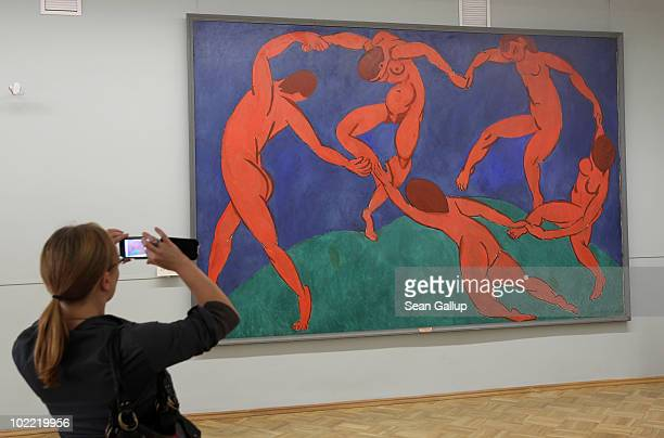A visitor takes a picture of the painting 'Dance' by Henri Matisse at the State Hermitage museum on June 19 2010 in St Petersburg Russia The State...