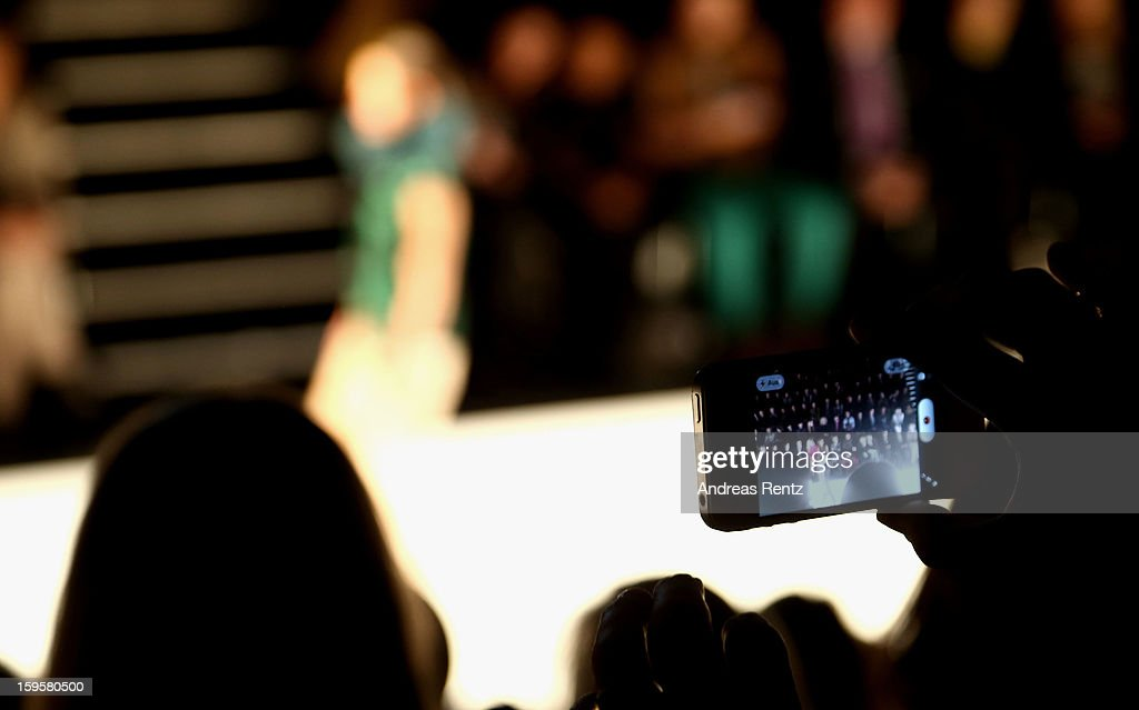 A visitor takes a picture of the runway with his smartphone at Mercedes-Benz Fashion Week Autumn/Winter 2013/14 at The Brandenburg Gate on January 16, 2013 in Berlin, Germany.