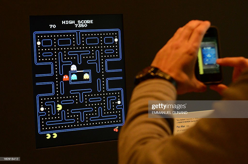 A visitor takes a picture of the video game Pac-Man (1980) during an exhibition preview featuring 14 video games acquired by The Museum of Modern Art (MoMA) in New York, March 1, 2013. The MoMA acquired 14 video games entering its collection as part of an ongoing research on interaction design. AFP PHOTO/EMMANUEL DUNAND