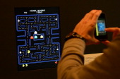 A visitor takes a picture of the video game PacMan during an exhibition preview featuring 14 video games acquired by The Museum of Modern Art in New...