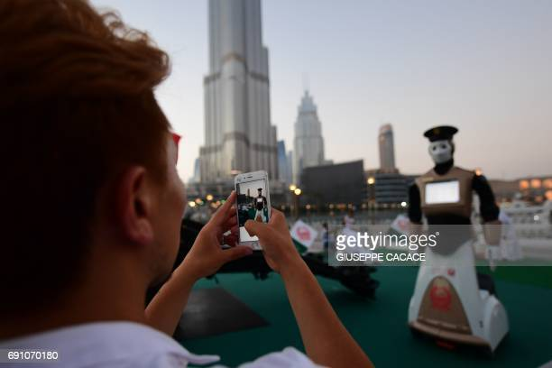 A visitor takes a picture of the world's first operational police robot near the Burj Khalifa in Downtown Dubai on May 31 as a military cannon is...
