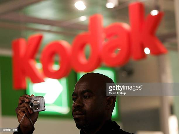 A visitor takes a picture with a digital camera near the Kodak stand at the CeBIT technology fair March 15 2007 in Hanover Germany CeBIT the world's...