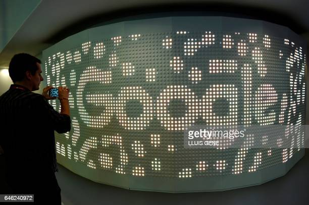 A visitor takes a picture with his mobile phone at the stand of Google on the second day of the Mobile World Congress on February 28 2017 in...