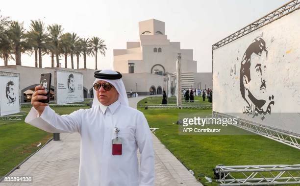 A visitor takes a selfie during an exhibition of artworks which were donated by members of the community depicting Qatari Emir Tamim bin Hamad...