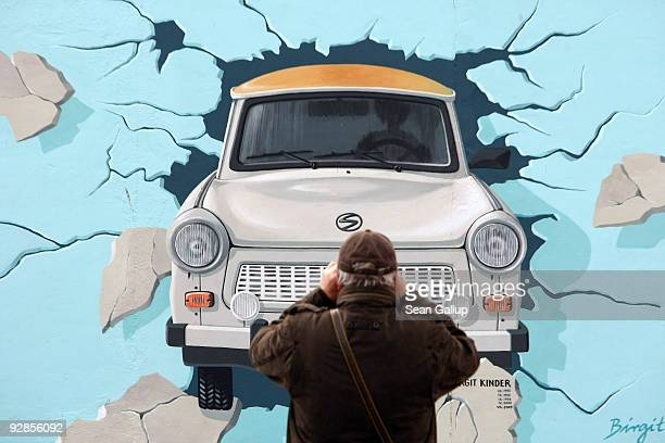 A visitor takes a snapshot of a restored mural showing a Trabant car breaking through the Wall along a stillexisting portion of the former Berlin...