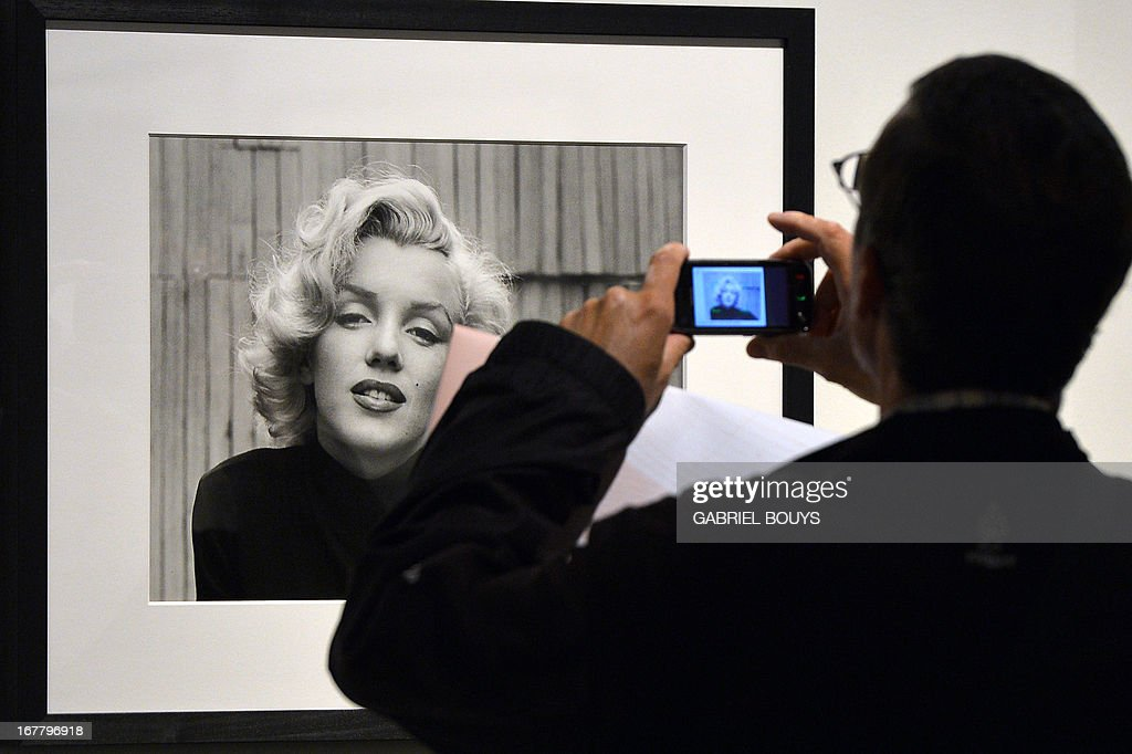 """A visitor takes a snapshot of Alfred Eisenstaedt's """"Marilyn Monroe, Hollywood, USA, 1953"""" during the 'Life. I grandi fotografi' (Life. The great photographers) exhibition at the auditorium on April 30, 2013 in Rome. The exhibition showing some 150 pictures taken from 1936 when the US magazine Life magazine premiered will be open from May, 1 to August 4, 2013. AFP PHOTO / GABRIEL BOUYS AFP PHOTO / GABRIEL BOUYS RESTRICTED TO EDITORIAL USE, MANDATORY CREDIT OF THE ARTIST, TO ILLUSTRATE THE EVENT AS SPECIFIED IN THE CAPTION"""