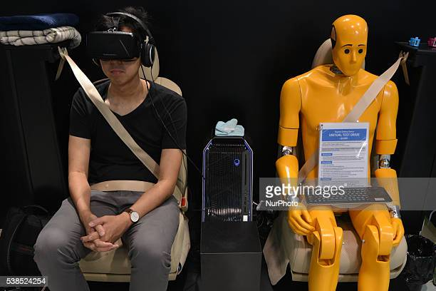 A visitor takes part in a virtual test drive using special glasses next to a crash test dummy at the Toyota show room in Tokyo Japan June 6 2016