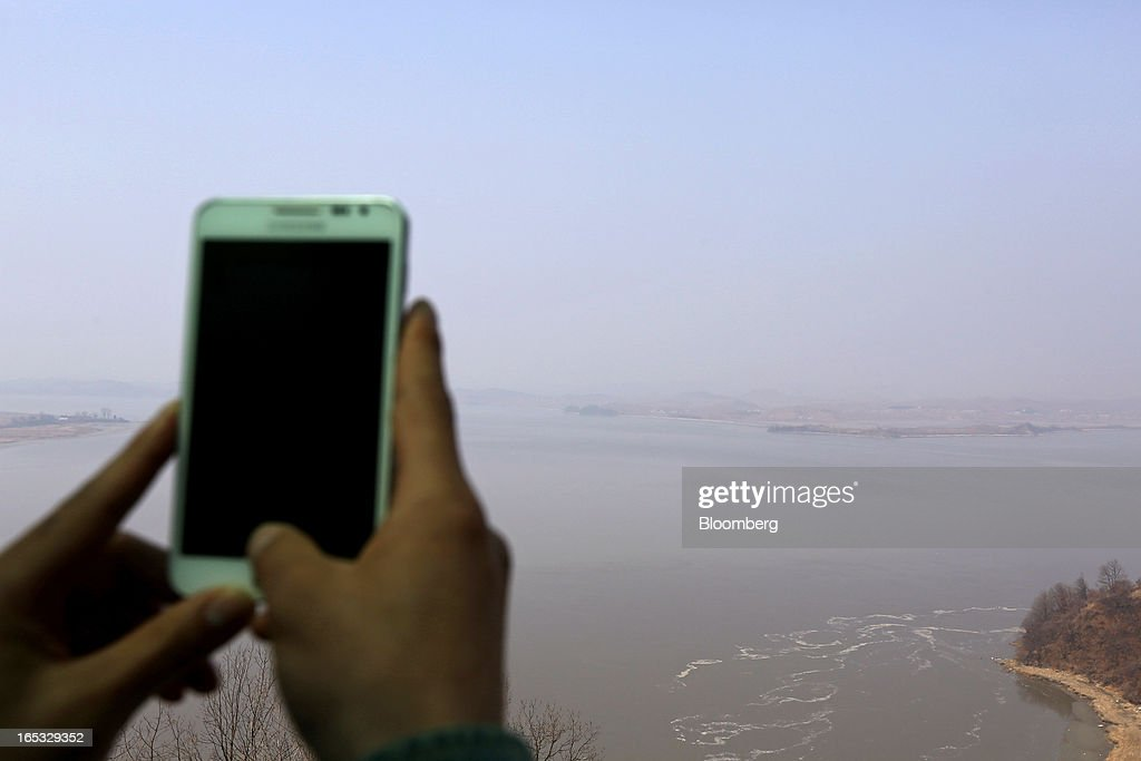 A visitor takes photograph of the North Korean village of Gaepung-Gun using a Samsung Electronics Co. Galaxy Note II smartphone at the Odusan Unification Observatory near the demilitarized zone (DMZ) in Paju, South Korea, on Wednesday, April 3, 2013. North Korea prevented South Korean workers from entering a jointly run industrial park today, adding to tensions after saying it will restart a mothballed nuclear plant and threatening to attack its southern neighbor. Photographer: SeongJoon Cho/Bloomberg via Getty Images