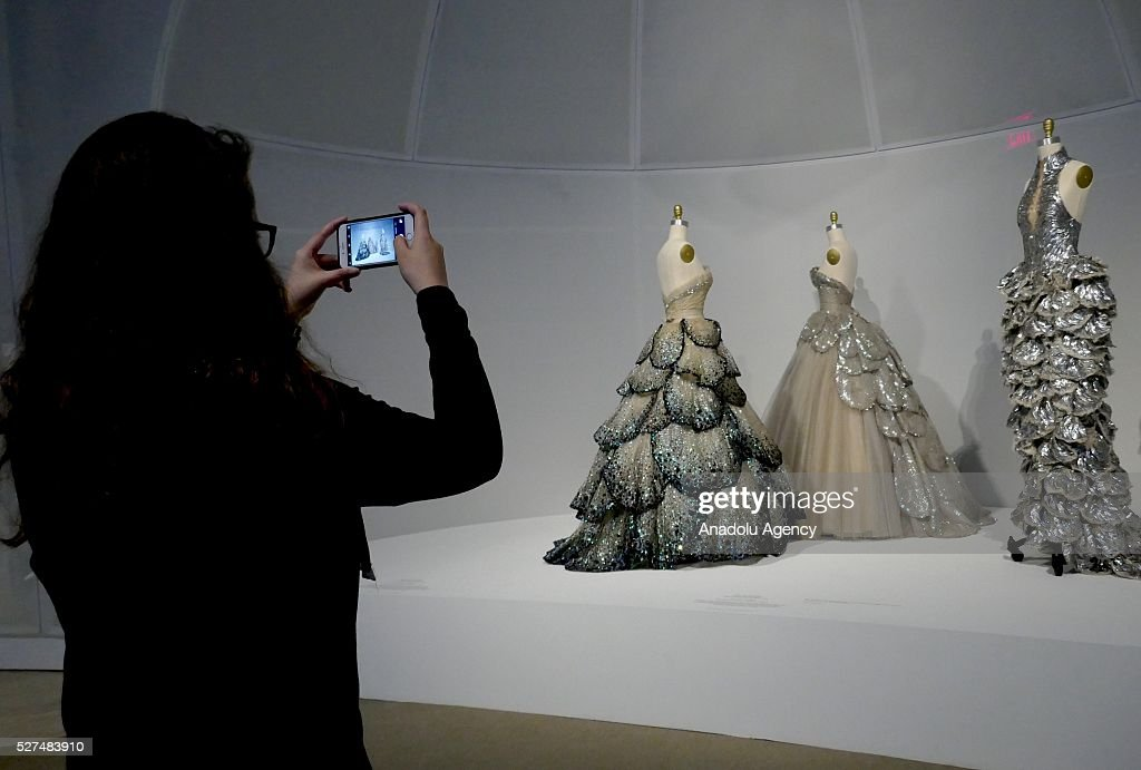 A visitor takes photographs of dresses during the 'Manus x Machina: Fashion In An Age Of Technology' Costume Institute Gala at Metropolitan Museum of Art on May 2, 2016 in New York City, United States.