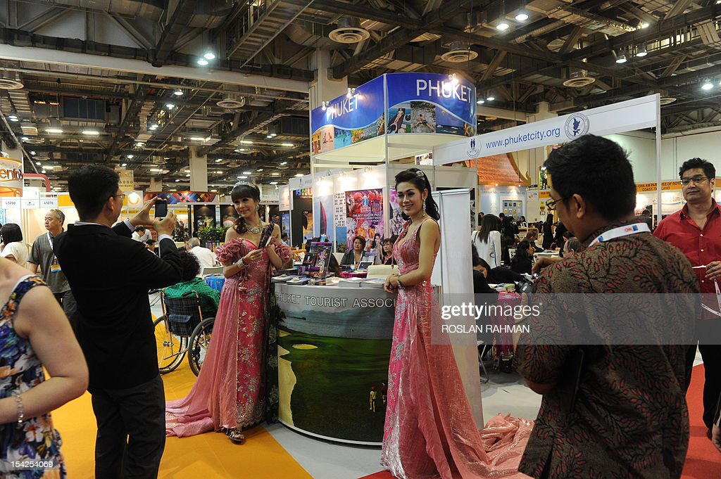 A visitor (L) takes photographs of promotional girls at a Phuket Tourist Association booth during ITB Asia, the trade show for Asian travel, in Singapore on October 17, 2012. More than 700 exhibitors from over 90 countries participate in the three-day trade event from October 17-19.