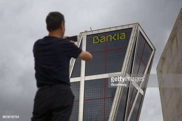 A visitor takes photographs outside the headquarters of Bankia SA at the Kio towers in Madrid on Wednesday June 28 2017 Bankia SA agreed to...
