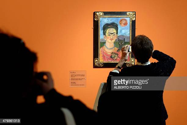 A visitor takes photos of the 'Selfportrait with the image of Diego on my breast and Maria on my brow' painting by Mexican artist Frida Kahlo during...