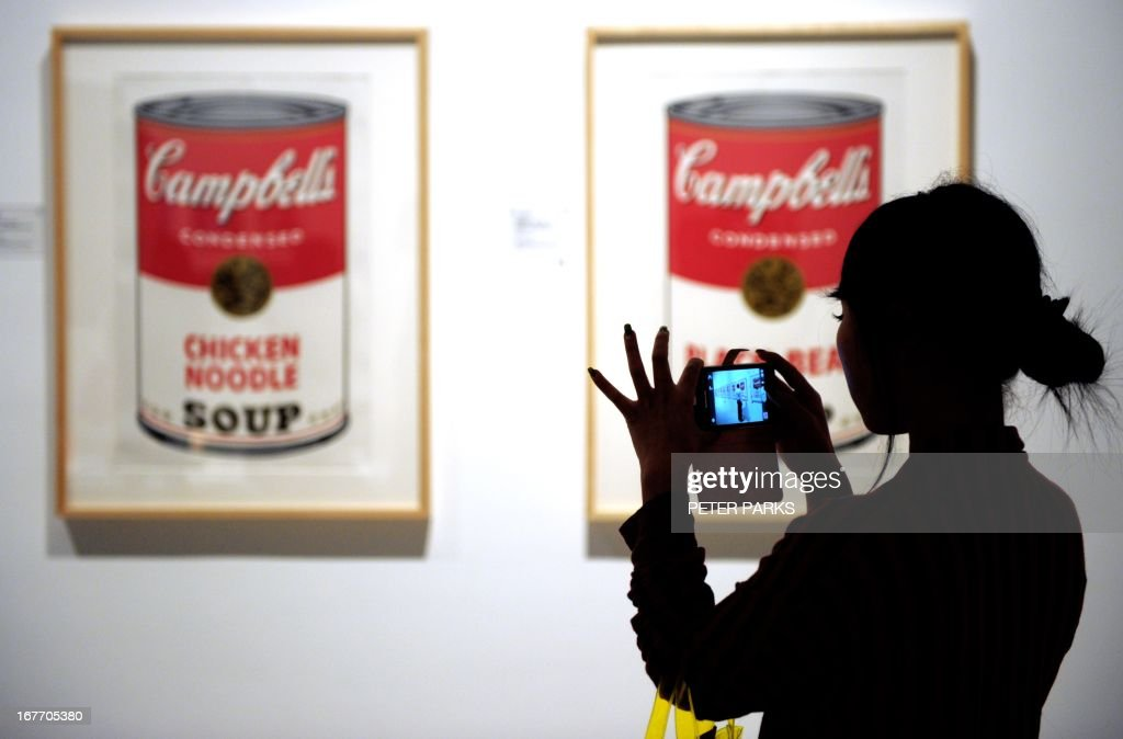 A visitor takes photos of works of art by US pop artist Andy Warhol at the exhibition 'Andy Warhol: 15 Minutes Eternal' showing at Shanghai's government-funded 'Power Station of Art' in Shanghai on April 28, 2013. Shanghai's contemporary art museum opened the show featuring the works of Warhol, but without his iconic portraits of former Chinese leader Chairman Mao. AFP PHOTO / Peter PARKS