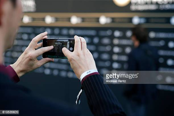 A visitor takes photos with his Huawei phone on the green carpet during the 12th Zurich Film Festival on September 26 2016 in Zurich Switzerland The...