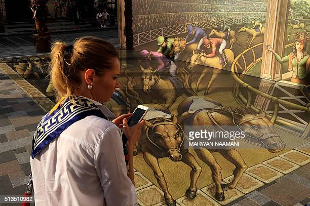 A visitor takes pictures of a 3D artwork on March 3 2016 near the Jumeirah Beach Residence in Dubai during the Canvas Festival a threedimensional...