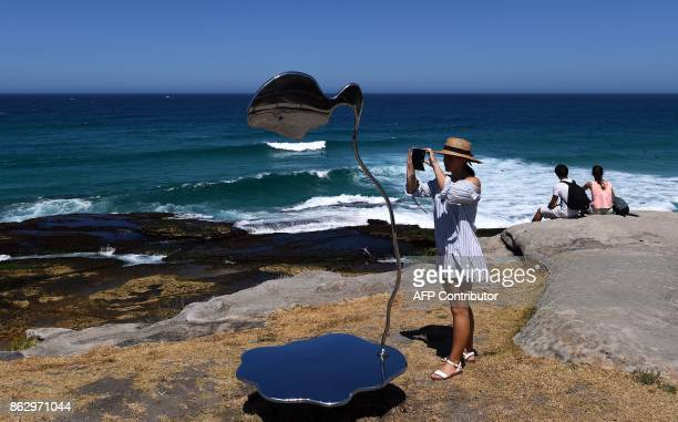 A visitor takes pictures of a sculpture by artist Hugh Mclachlan at the 'Sculpture by the Sea' exhibition near Bondi beach in Sydney on October 19...