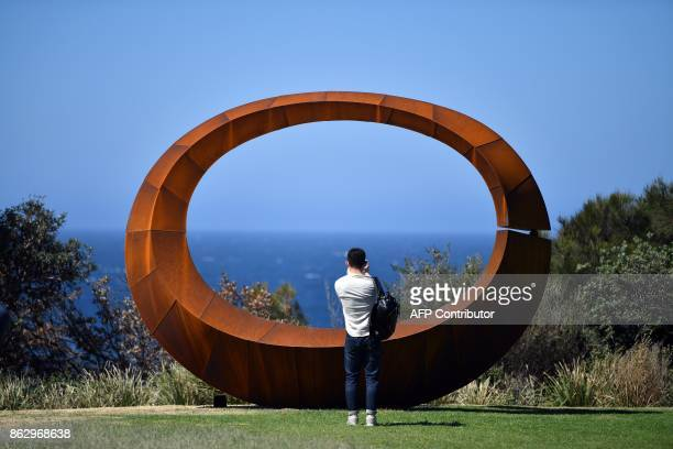 A visitor takes pictures of a winning sculpture by artist David Ball that is part of the 'Sculpture by the Sea' exhibition near Bondi beach in Sydney...
