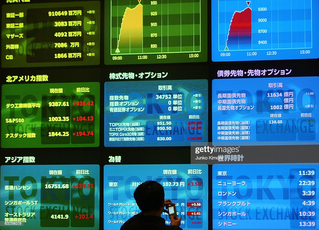 A visitor takes pictures of an electoric board displaying the Nikkei Index and other figures at Tokyo Stock Exchange on October 14 2008 in Tokyo...