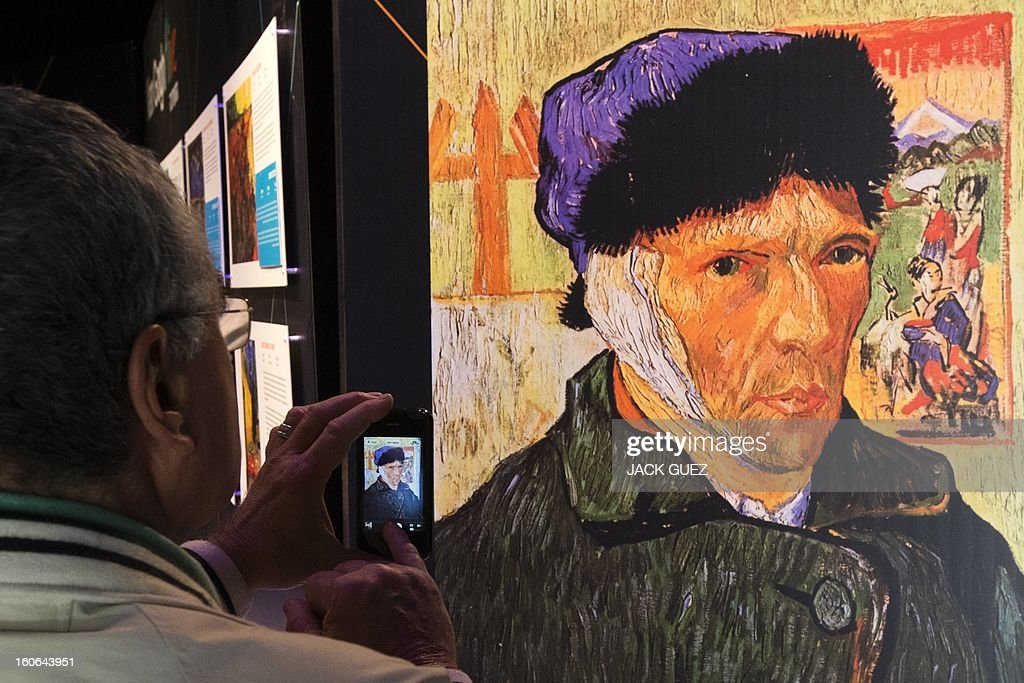 A visitor takes pictures of at giant screen featuring a self-portrait by Dutch painter Vincent van Gogh displayed during a traveling multimedia art exhibition entitled 'Van Gogh alive' on February 4, 2013 at the Israel Trade Fairs and Convention Center in Tel Aviv. The interactive installation, featuring thousands of 360-degree lifelike images of Van Gogh's works, has already toured Turkey, Singapore and the United States and will take place in Tel Aviv until March 4, 2013. AFP PHOTO / JACK GUEZ