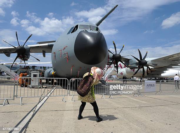 A visitor takes pictures of the Airbus A 400M on the tarmac at the International Paris Airshow at Le Bourget on June 16 2015 AFP PHOTO ERIC PIERMONT