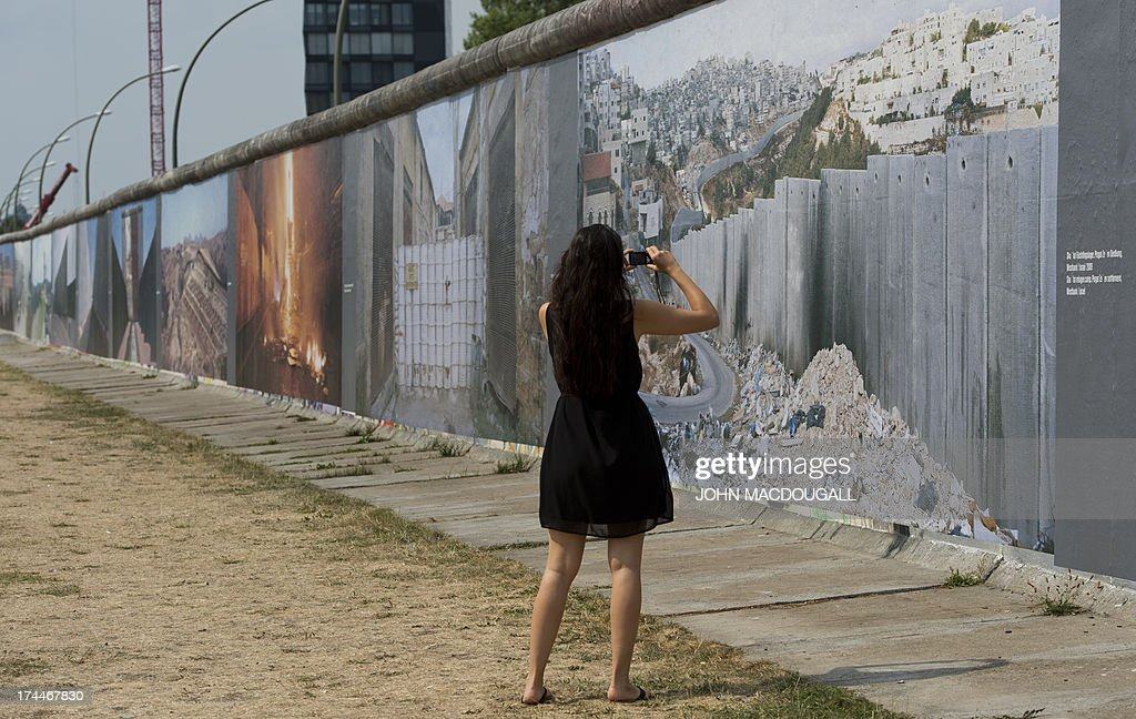 A visitor takes pictures of the 'Wall on Wall' exhibition by German photographer Kai Wiedenhoefer, displayed on a remaining section of the Berlin wall July 26, 2013. Wiedenhoefer's 'Wall on Wall' project features giant panoramic photographs of walls taken in Northern Ireland, Iraq, Cyprus, the West Bank, Morocco, South Korea and the border between the United States and Mexico. The exhibition takes place between10 July and 13 September 2013.