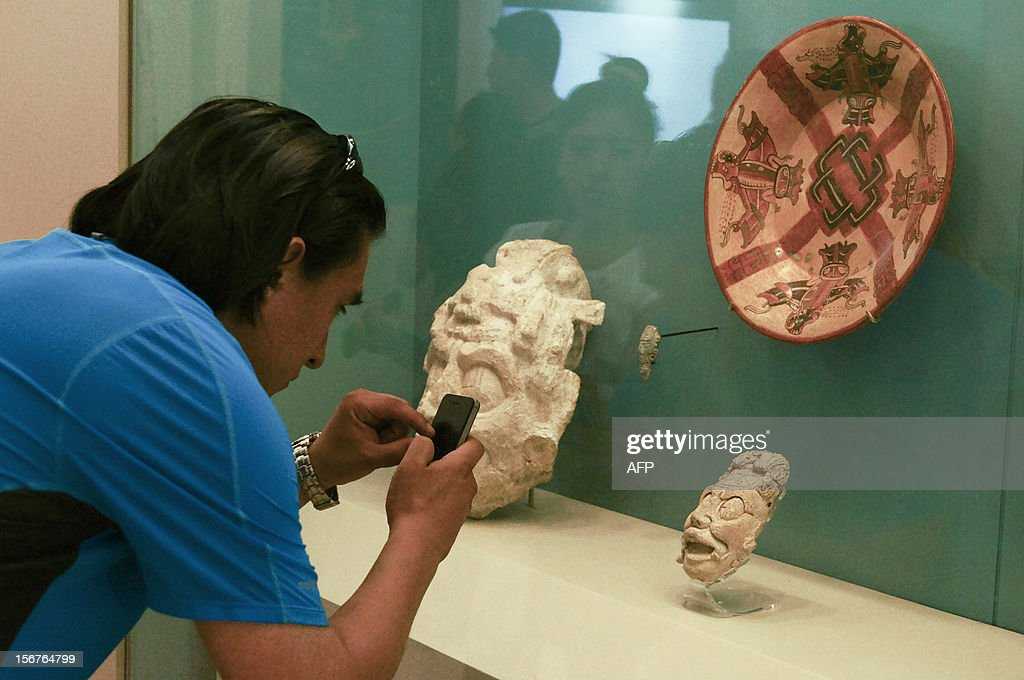 A visitor takes snapshots of Mayan art pieces with a mobile phone at the Mayan Museum in Cancun, Mexico on November 18, 2012. Mexico's National Institute of Archaeology and History (INAH), custodian of the archaeological sites, will offer throughout December a series of conferences, academic and artistic events, with an emphasis on informing and disseminating the legacy of the Maya and diminish the catastrophist visions. AFP PHOTO/JOSE DOMINGUEZ BARRERA