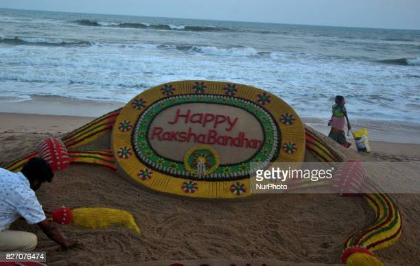 A visitor taking pictures of a sand art creating by sand artist Sudarshan Pattnaik on the eve of Indian Hindu festival Rakha Bandhan at the Bay of...