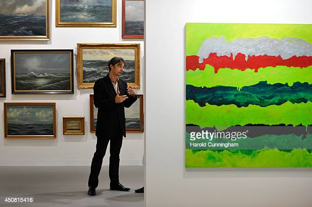 A visitor talks in The Modern Institute gallery of Art Basel on June 18 2014 in Basel Switzerland Art Basel one of the most prestigious art fair in...