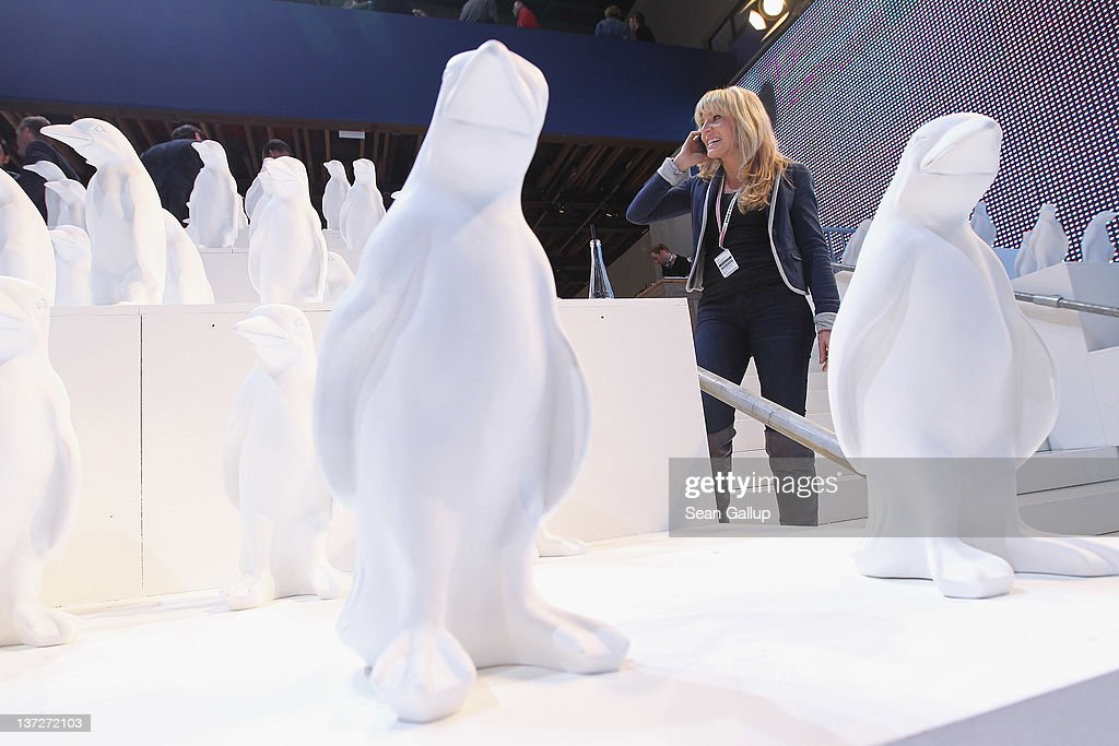 A visitor talks on a mobile phone next to effigies of penguins at the Hilfiger Denim stand at the 2012 Winter Bread And Butter fashion trade fair at former Tempelhof Airport on January 18, 2012 in Berlin, Germany. Bread And Butter is a semi-annual event and is among Europe's major fashion trade fairs.
