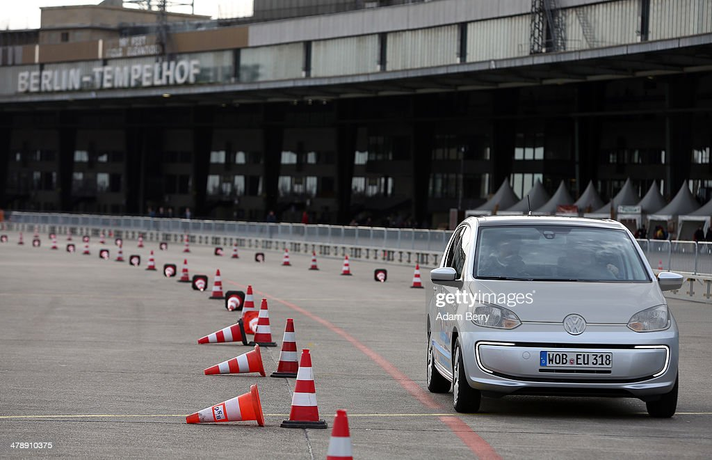 A visitor test drives an electric Volkswagen e-up! automobile at the Electric Mobility Week (e-Mobilitaetswochen), a public Volkswagen (VW) event at the former Tempelhof airport, on March 15, 2014 in Berlin, Germany. The event was designed to promote the company's e-Golf und e-up! automobiles, as well as its other alternative energy powered vehicles.